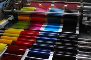 an offset printing press with CMYK ink rollers