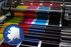ak map icon and an offset printing press with CMYK ink rollers
