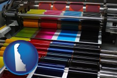de map icon and an offset printing press with CMYK ink rollers