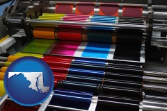 md map icon and an offset printing press with CMYK ink rollers